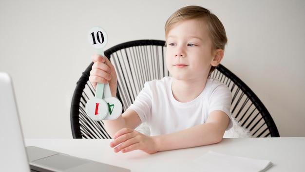 Dziecko posiadające numery do internetowego kursu matematyki