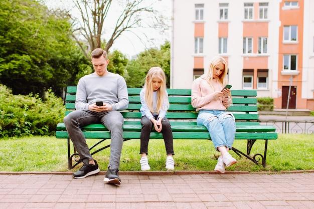 Dziecko pozostaje smutne i bez opieki, podczas gdy jej rodzice gubią się w telefonach komórkowych.