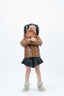 Dziecko pozuje z torbą na białym tle.