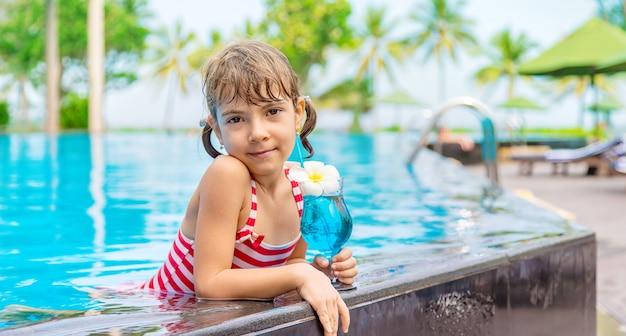 Dziecko przy basenie pije koktajl