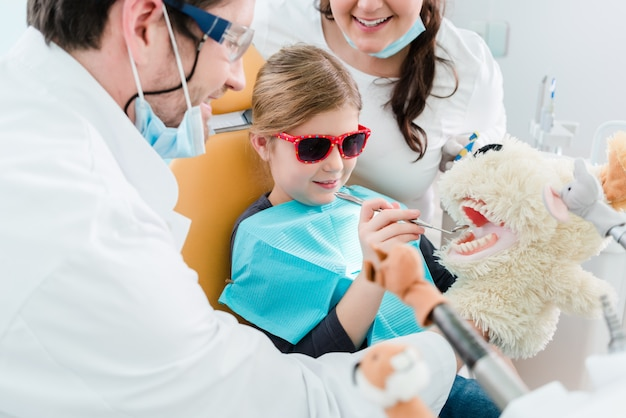Dziecko przy dentysty biurowym patrzejący zęby zwierzęcia domowego zabawka