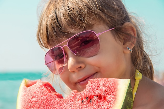 Dziecko przy morzem je arbuza. s
