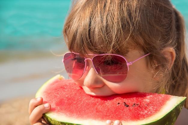 Dziecko przy morzem je arbuza.