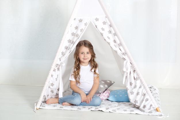 Dziecko przygotowuje się do pójścia do łóżka. przyjemny czas w przytulnej sypialni. mała dziewczynka siedzi w tipi z kolorowymi poduszkami w swoim pokoju. dekorowanie pokoju dziecięcego namiotem do gry. dziecko bawi się.