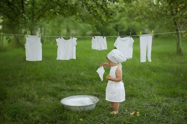 Dziecko radośnie pierze swoje ubrania w misce