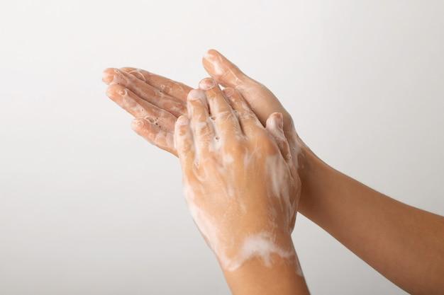 Dziecko ręce baniek mydlanych na szarej ścianie