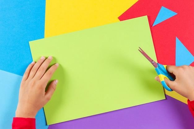 Dziecko ręce cięcia kolorowy papier nożyczkami