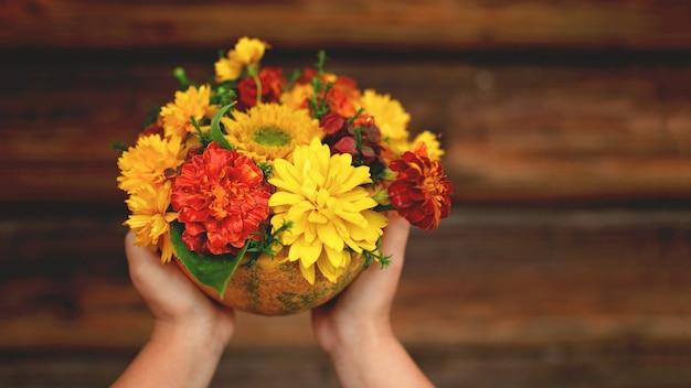 Dziecko ręce trzyma piękną kompozycję naturalnej dyni z pomarańczowymi i żółtymi kwiatami w nim, nad drewnianym wiejskim tłem, sezonem jesiennym i koncepcją wakacji dziękczynienia