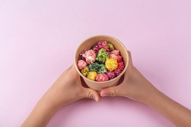 Dziecko ręce trzymając pudełko z popcornu cukierki karmelowe kolorowe tęczy na różowym tle. koncepcja przekąsek kina. oglądanie filmów i rozrywki. układ płaski.