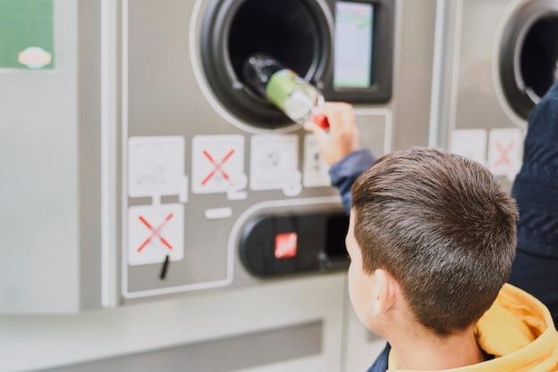 Dziecko recykling plastikowych butelek w maszynie