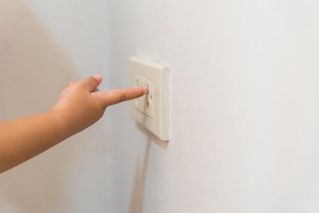 Dziecko ręka bawić się z elektrycznym gniazdkiem, niebezpieczna sytuacja w domu.