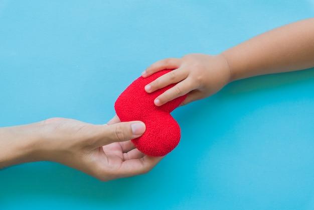 Dziecko ręka daje czerwonemu sercu jej tata, szczęśliwi relacje rodzinni