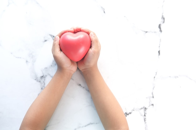 Dziecko ręka trzyma czerwone serce na białym tle