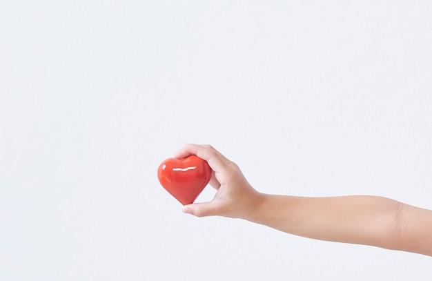 Dziecko ręka trzyma czerwone serce na lekkiej ścianie.