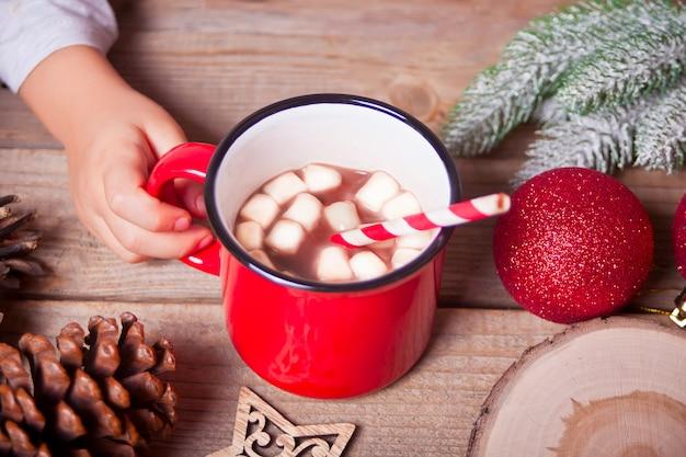 Dziecko ręka trzyma czerwony kubek kakao boże narodzenie na drewnianym stole