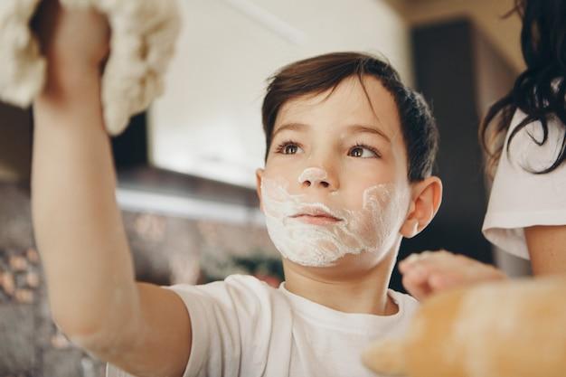 Dziecko robi ciasta. dzieci były pokryte mąką. kolacja w piekarni. uczta w kuchni