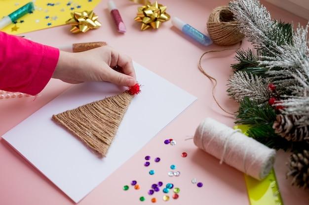 Dziecko robi kartkę świąteczną na ferie zimowe. rękodzieło i rękodzieło na boże narodzenie
