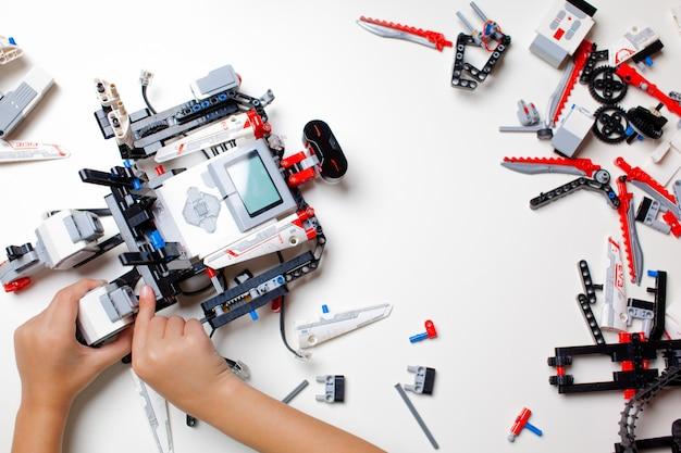 Dziecko robi robota z przypadkowych elementów