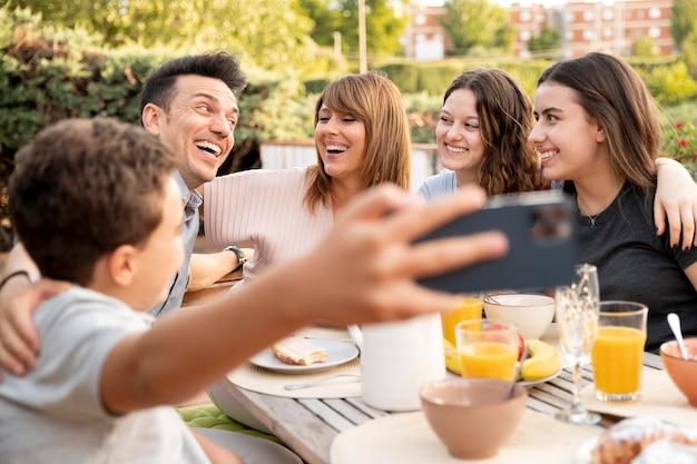 Dziecko robi selfie rodziny jedzącej razem lunch na świeżym powietrzu