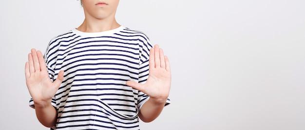 Dziecko robi znak stop z dłoni. baner z miejsca na kopię. chłopiec pokazuje gest stop z palmą.