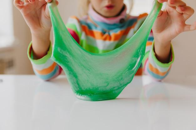 Dziecko rozciąga śluz na boki. ręce dzieci bawią się w szlam. robienie szlamu. miejsce. selektywne skupienie. układ tekstu.