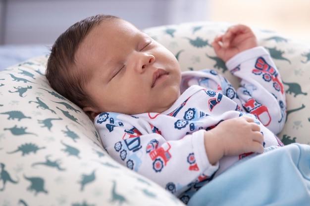 Dziecko rozluźnione w łóżku, śpiące iz podniesioną ręką.