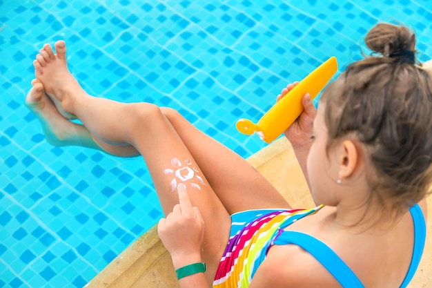 Dziecko rozmazuje krem przeciwsłoneczny na nodze.