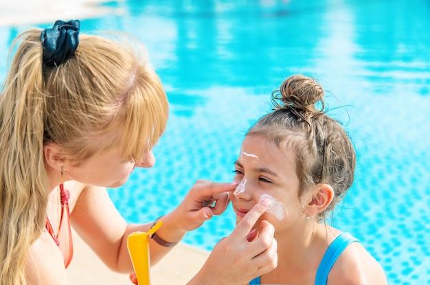 Dziecko rozmazuje matkę kremem z filtrem