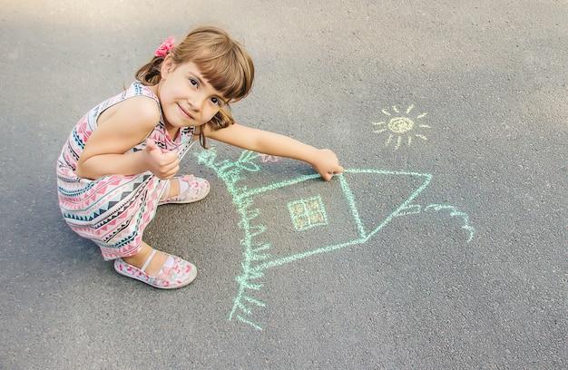 Dziecko rysuje dom kredą na asfalcie. selektywne skupienie.