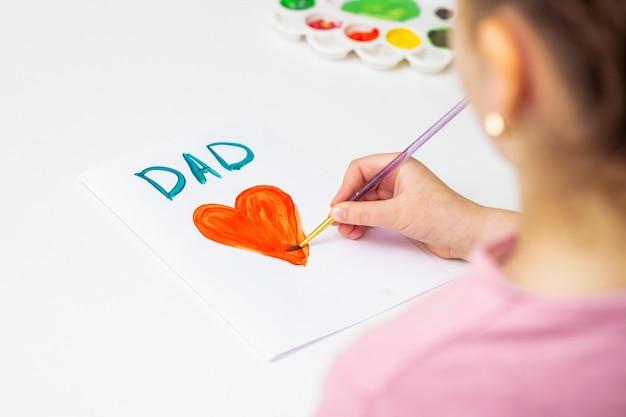 Dziecko rysuje dzień ojca kartkę z życzeniami.