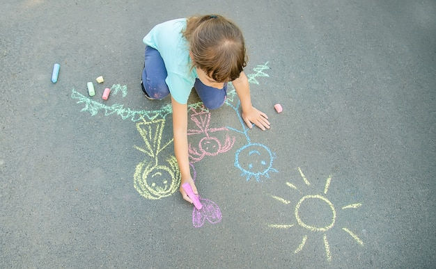 Dziecko rysuje kredą rodzinę na chodniku. selektywne skupienie.