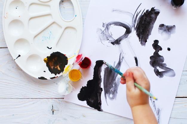 Dziecko rysuje pędzlem i maluje widok z góry