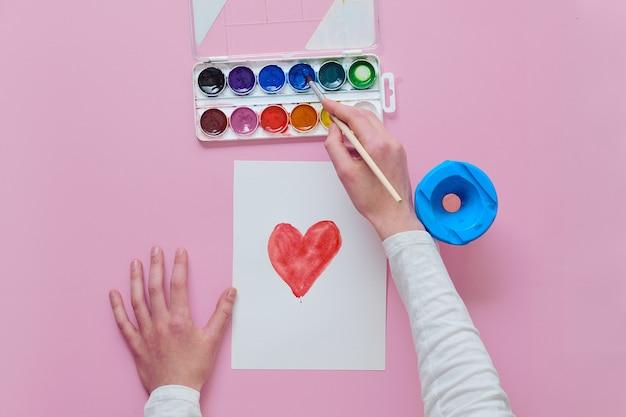 Dziecko rysuje serce, używa pędzla i farb akwarelowych