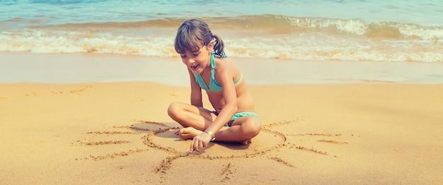 Dziecko rysuje słońce na plaży