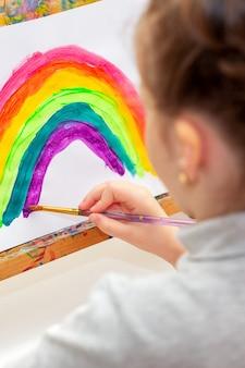 Dziecko rysuje tęczę.