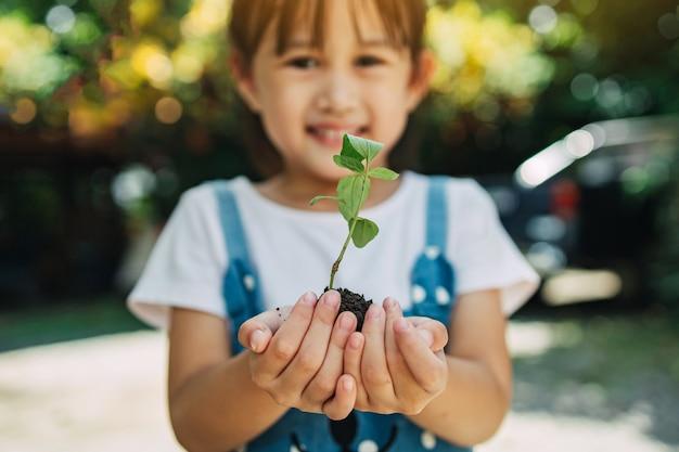 Dziecko sadzi drzewo, aby pomóc w zapobieganiu globalnemu ociepleniu lub zmianom klimatu i ratowaniu ziemi