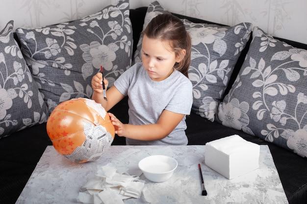 Dziecko siada na sofie i robi z balonu dynię z papier-mache na halloween