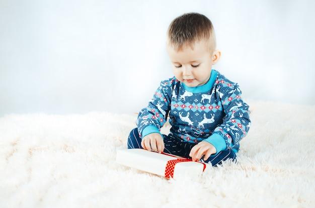 Dziecko siedzące na łóżeczku i bawiące się pakowanymi prezentami, sylwester w sweterku w renifera