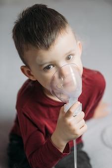 Dziecko siedzące na łóżku w sypialni samodzielnie wykonuje inhalację