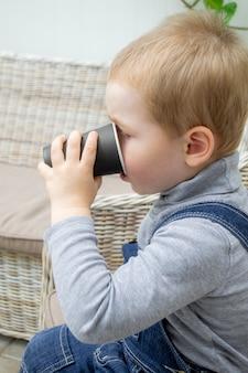 Dziecko siedzi i pije gorące kakao z jednorazowego papierowego kubka. chłopczyk w szarym swetrze i dżinsowym kombinezonie z czarnym szkłem w rękach.