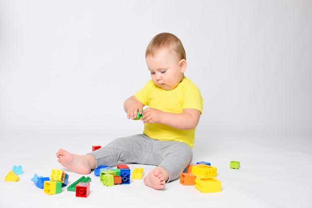 Dziecko siedzi na białym tle w żółtej koszulce i bawi się w zestaw konstrukcyjny. dzieciak jest szczęśliwy i zbiera konstruktora