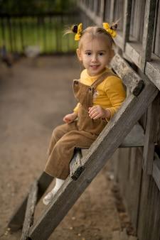 Dziecko siedzi na drabinie przy kurniku na podwórku farmy