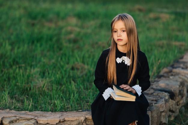 Dziecko siedzi na kamiennej ławce, trzyma w rękach książkę i patrzy w dal.