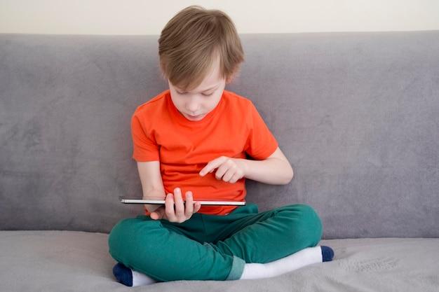 Dziecko siedzi na kanapie i za pomocą cyfrowego tabletu