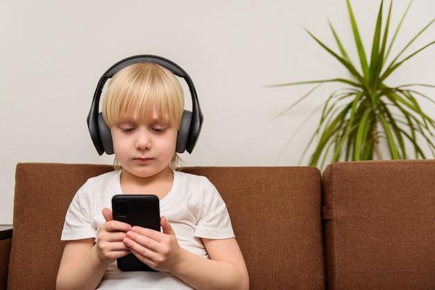 Dziecko siedzi na kanapie ze słuchawkami i patrzy na telefon. koncepcja uzależnienia od dzieci i gadżetów