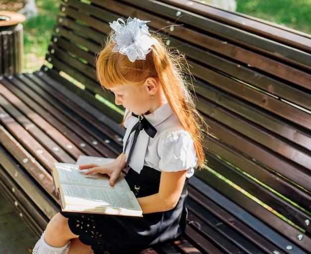 Dziecko siedzi na ławce na zewnątrz w ciepły słoneczny dzień i wraca do szkoły. odpocznij po szkole w parku.