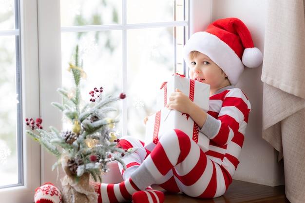 Dziecko siedzi na parapecie szczęśliwe dziecko w świątecznej piżamie