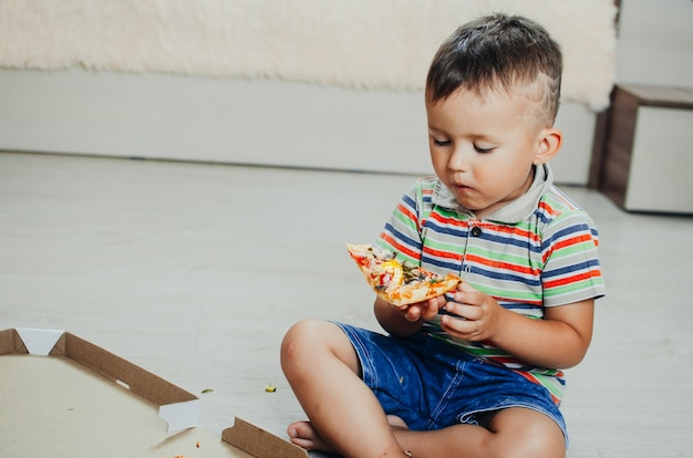 Dziecko siedzi na podłodze i je pizzę bardzo apetycznie i zachłannie, w szortach i koszulce