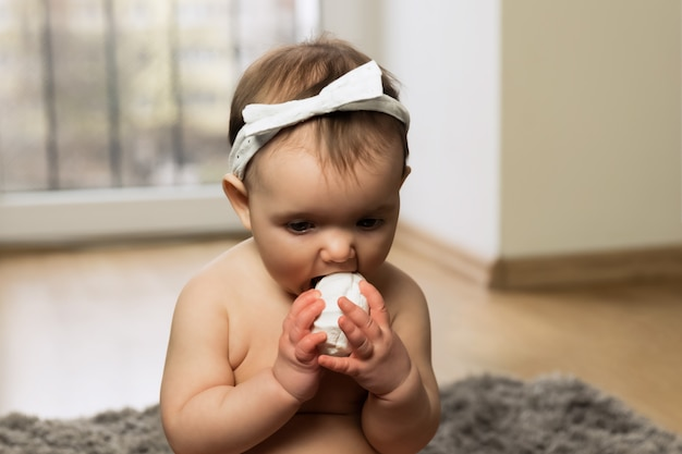 Dziecko siedzi na podłodze w pieluszce i zjada pianki. zabronione nie jest zdrowy posiłek.