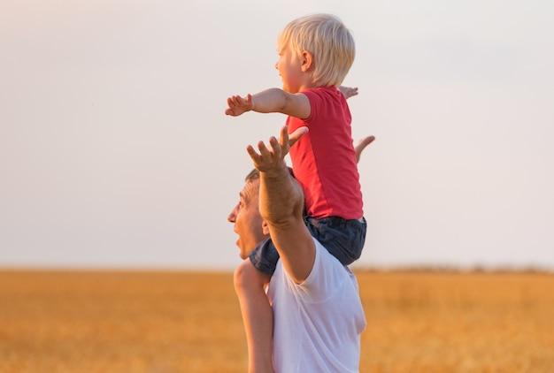 Dziecko siedzi na ramionach ojca i ręce do góry